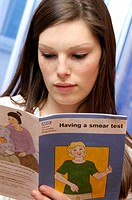 Cervical smear information. Woman reading a NHS leaflet on cervical smears.