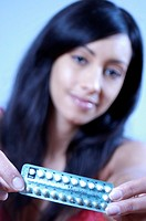 Contracpetive pills. Young woman preparing to take oral contraceptive pills. These contain synthetic versions of one or both of the female sex hormone...