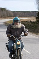 A man with a big beard on a motorcycle
