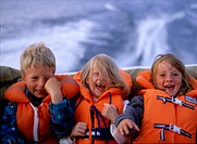 Kids on a boat in life jackets
