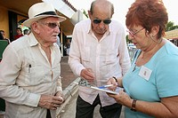 Art Walk, monthly event, Hispanic senior female, surveying males. Calle Ocho, Little Havana, Miami. Florida. USA.