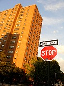 Bright red stop sign composed with a leaning New York City project housing building. Brigh blue sky in the background. USA