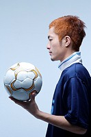 Side view of soccer player holding ball