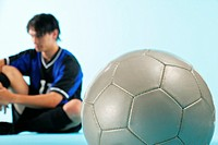 Soccer player sitting with ball in foreground
