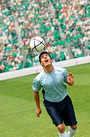 Soccer player juggling ball on head