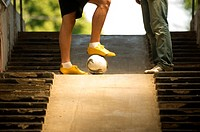 Teenage boys with foot on ball on steps
