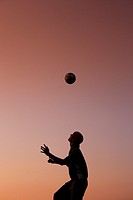 Silhouette of man juggling ball on head