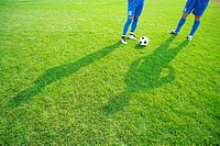 Shadows of two soccer players with ball