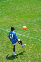Soccer player juggling ball on sideline