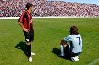 Two soccer players waiting on pitch