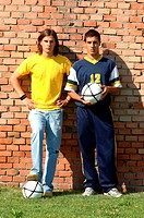 Young friends with soccer ball in front of brick wall
