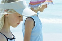 Girls walking on sandy beach, close up