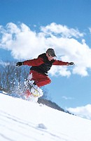 Boy snowshoeing mid air