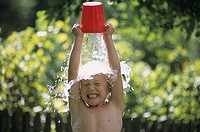 Boy spilling water over his head