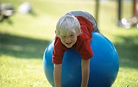 Boy lying on a big blue rubber ball