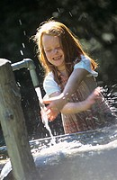 girl playing with the water of a fountain