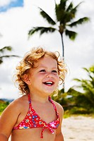 Little girl with blond curly hair plays on the beach, palm tree behind