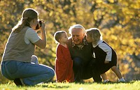 Grandfather and grandchildren embracing and posing for a camera in the park.