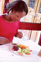 Portrait of a woman enjoying a healthful vegetable salad. (c) Laurent/Gabjo