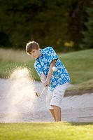 Boy, age 14, hitting out of sandtrap on golf course. McCall, Idaho USA