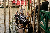 Tronchetto gondola with businessman on phone at Ca d'Oro, Cannaregio. Venice. Veneto, Italy