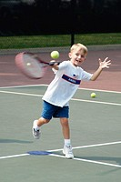 4 and 5 year old children take group tennis lessons taught by college students at a public tennis court