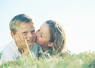 Boy and girl lying on grass, girl kissing boy on cheek