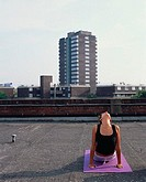 Woman doing yoga on roof