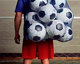 Footballer holding a bag of footballs