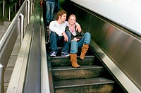 Couple sitting on escalator