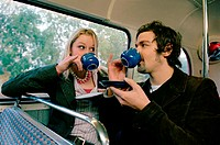 Couple drinking tea on bus