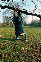 Man hanging on tree branch