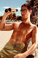 Man using binoculars on beach