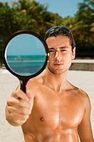 Man on beach holding hand mirror