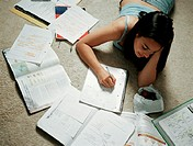 Girl doing homework on floor