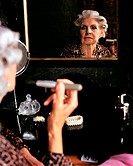 Glamourous senior woman applying makeup