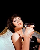 Glamourous young woman drinking a cocktail