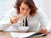 Office worker eating spaghetti
