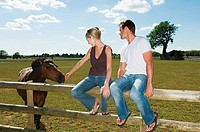 Couple sitting on a fence with horse