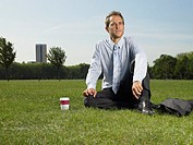 Male office worker sitting in the park