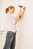 young woman putting a nail into the wall