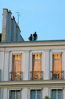 Two men on the roof. Three windows. Evening. Buiding of Saint Louis island. Paris. France