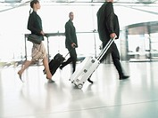 Business people pulling their suitcases through an airport