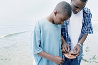 Father and son examining a small crab on the beach