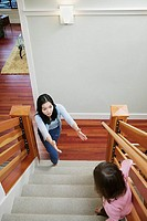 Mother reaching for daughter on stairs