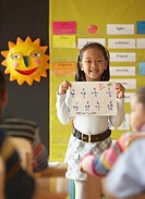 Young girl in classroom holding up math sheet