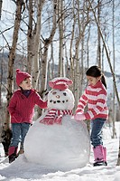 Two girls building snowman