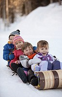 Friends sledding on toboggan
