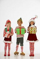Portrait of children dressed as elves holding gifts