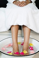 Woman´s feet soaking in rose water